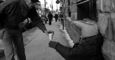 Giving coffee to a homeless person